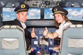 Fotografia felice piloti nella cabina di pilotaggio con pollice in alto
