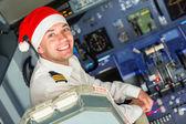 Fotografia pilota nella cabina di pilotaggio con cappello santa