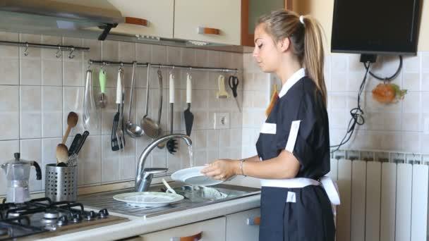 Hausmädchen spült Geschirr in der Küche