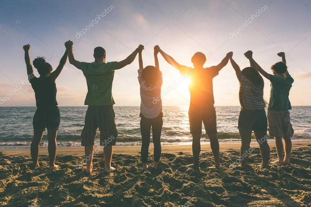 People with Raised Arms looking at Sunset