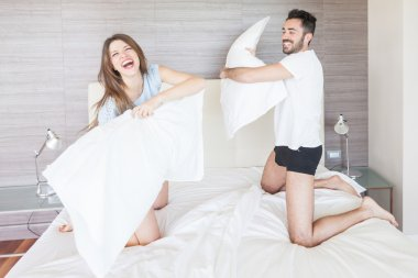 Happy Couple Having Pillow Fight in Hotel Room