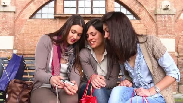 drei Frauen, die Fotos in die Kamera schauen