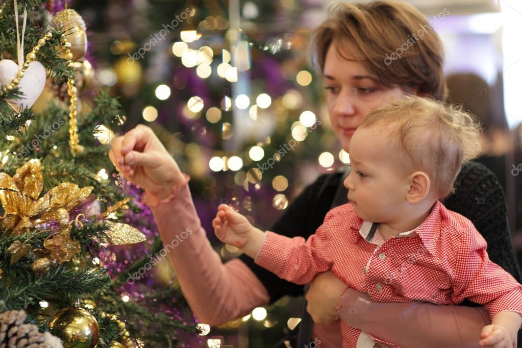 Family dressing Christmas tree — Stock Photo © AChubykin #17384099
