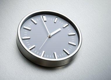 Metal clock on the wall of steel