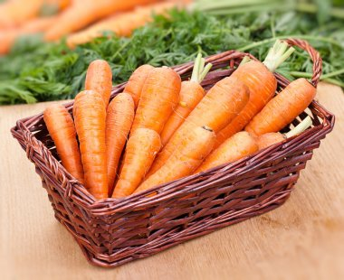 Fresh carrots in a basket on the table