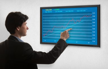 Businessman checking stock market on screen
