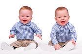 Dvojčata chlapci sedět, samostatný