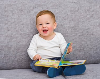 The one-year-old kid sits with the book