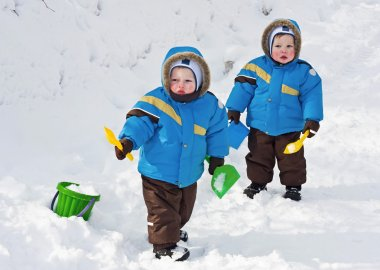 One-year-old twins play in snow together