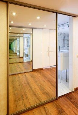 Sliding-door mirror wardrobe in modern hall interior with infini