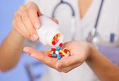 Fotografie prášky, tablety a drogy z láhve v rukou lékaře