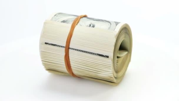 Drehend zusammengerolltes Bündel von 100-Dollar-Scheinen auf weißem Hintergrund
