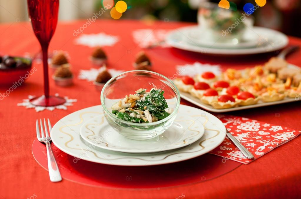 Decorated Christmas dining table with delicious salad (spinach,