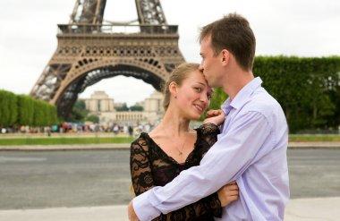 Happy couple in love in Paris near the Eiffel Tower