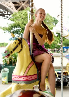 Beautiful young girl having a ride on Parisian marry-go-round