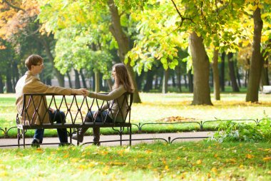 Dating couple on a bench by fall