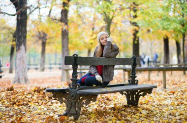 Young girl sitting on a bench in park