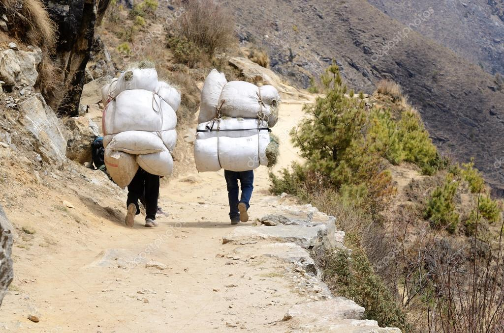 Two sherpa porters carrying heavy sacks in Himalayas,Nepal