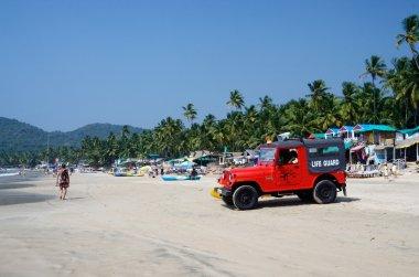 Life guard red car watching for tourists enjoying  Palolem beach,Goa,India