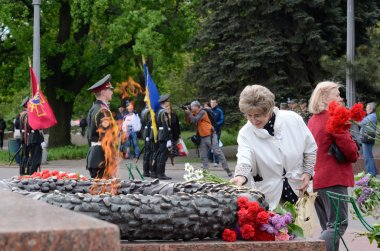 Old lady put flowers to Eternal Flame in commemoration of Soviet soldiers who fought against Nazi invasion during Second World War,Odessa,Ukraine