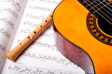 Wooden flute and classic acoustic guitar on sheet music. Close up.