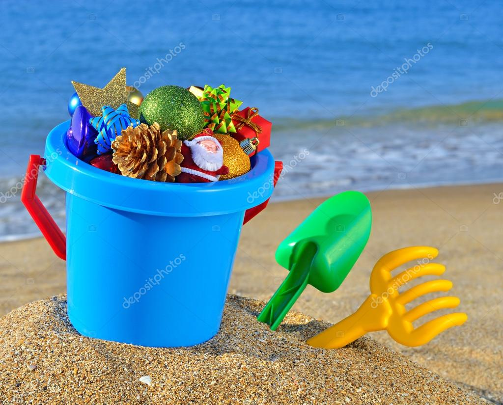 christmas decorations in a baby bucket and toys on the beach