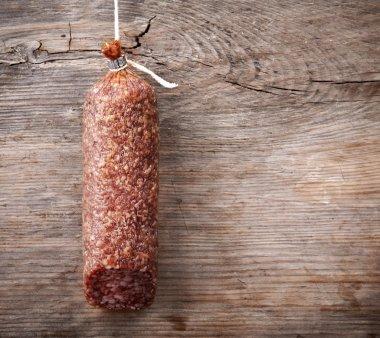 Hanging salami sausage on wooden background