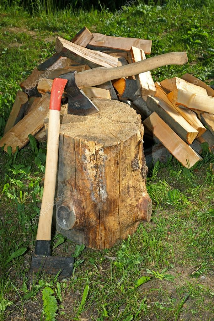 Axe splitting hammer and cut fire wood on a green grass
