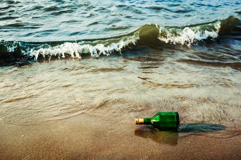 Message bottle on beach in waves
