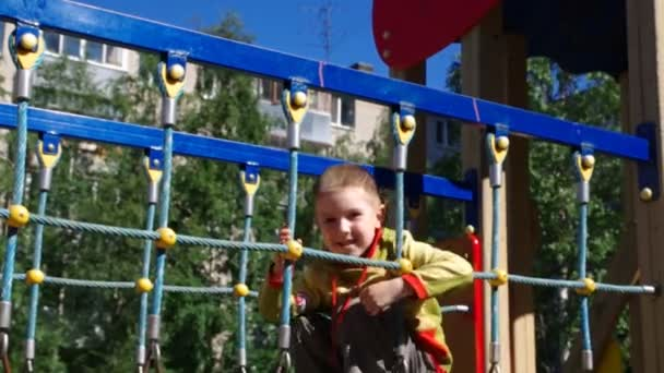 Cute little boy playing in a children playground .