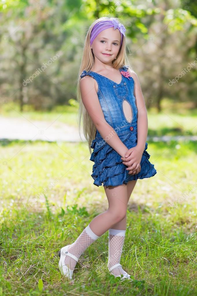 Little blond girl in jeans dress