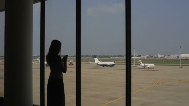 dívka mluví o mobilní telefon na letišti
