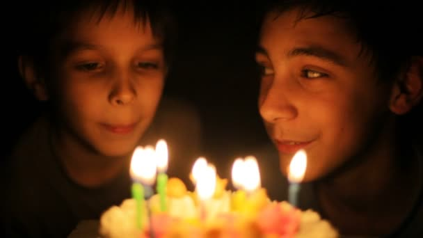 Boys blow out candles on birthday cake