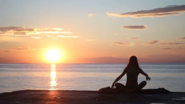 silueta ženy jógy na moře slunce