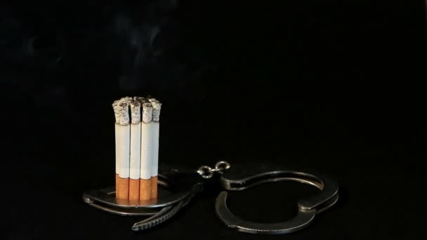smoldering cigarette in handcuffs on black background, Timelapse