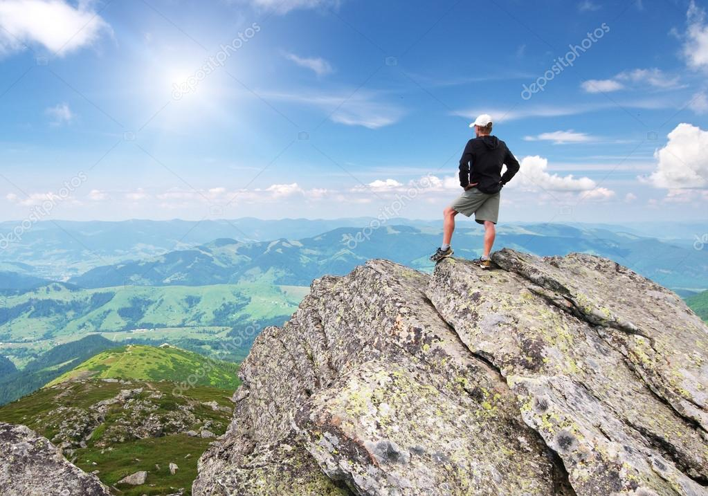 Man on peak of mountain.