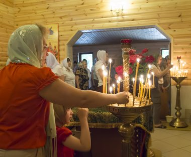 A woman lights a memorial candle