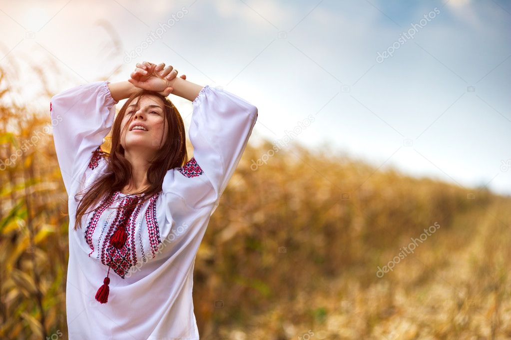 Woman in traditional shirt standing on cornfield