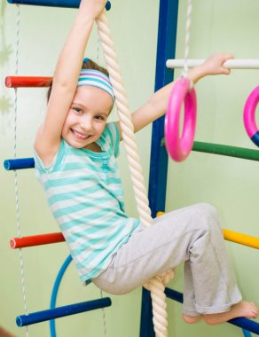 Happy little girl at home gym