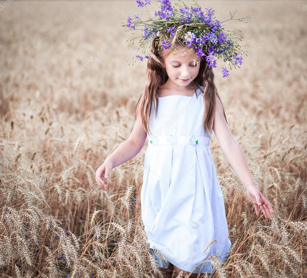 beautiful little girl in a field of wheat