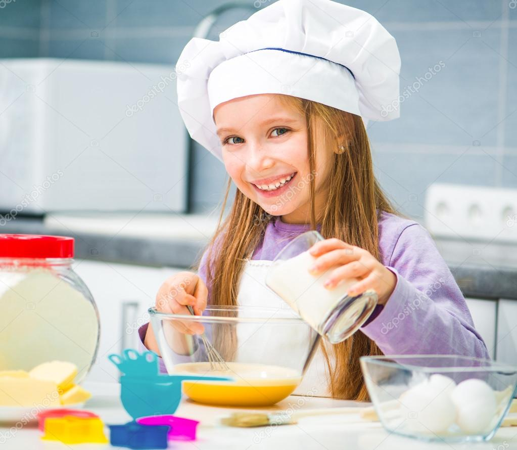 Cute Little Girl In The Kitchen Preparing Cookies