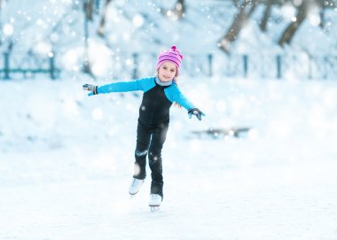 Cheerful little girl in thermal suits skating outdoors