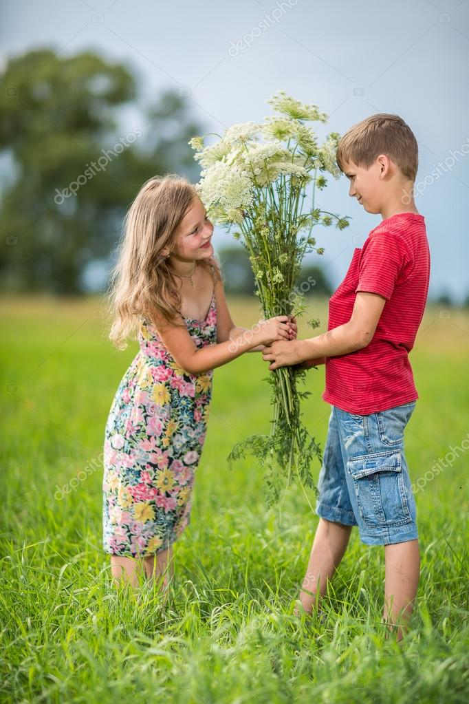 Spring. Boy gives girl a bouquet of flowers .