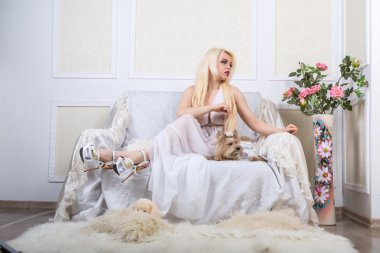 Blonde woman in a white dress with a dog