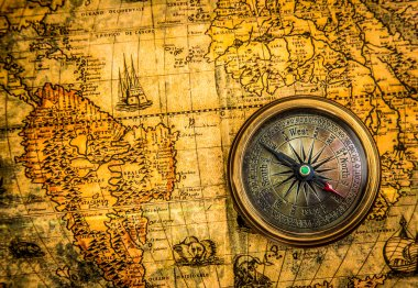 Vintage compass lies on an ancient world map