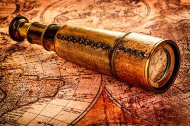 Vintage spyglass lies on an ancient world map