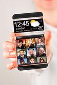 Fotografia smartphone con schermo trasparente in mani umane