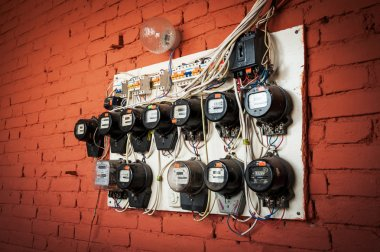 old electric meters on a red brick wall