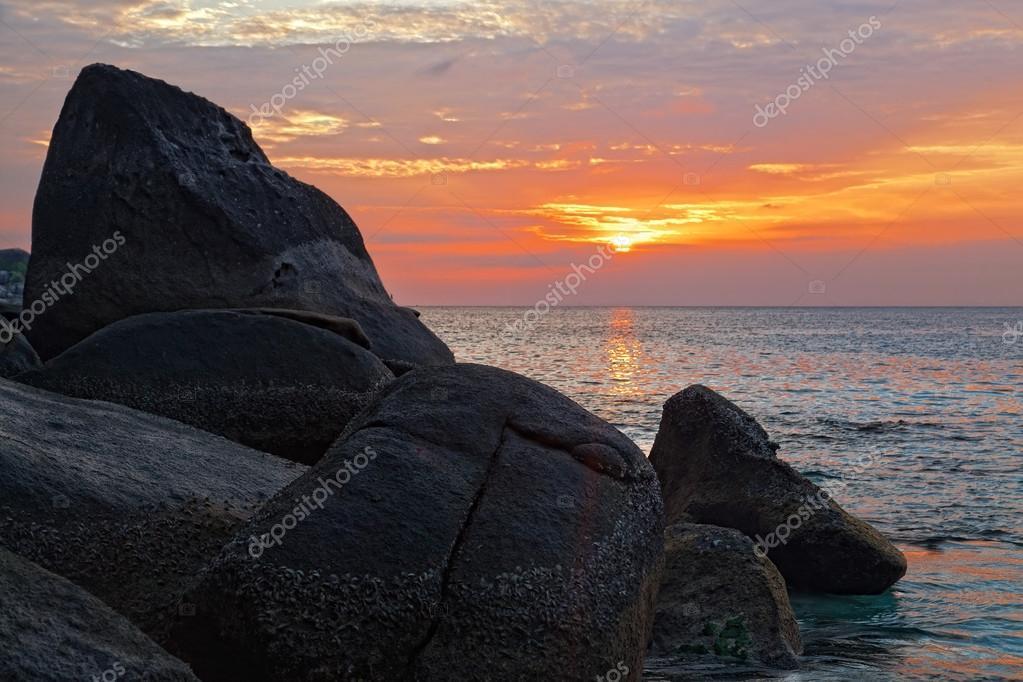 Big stones on an ocean coast against a sunset in tropics, Thailand