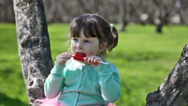 malá holčička v tyrkysové bundě jí cukr cukroví, sedí na stromě